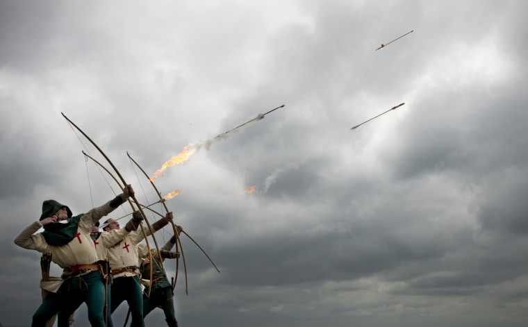 Purbrook Bowmen fire a volley of fire arrows from Southsea Castle into The Solent towards where the 16th century Tudor warship Mary Rose sank in 1545 in Portsmouth, southern England. Britain's King Henry VIII watched the warship sink from the castle. The day-long event will mark the symbolic journey of the ship's bell as the last artafact to be placed into the new Mary Rose Museum ahead of its public opening on May 30. (Adrian Dennis/Getty Images)