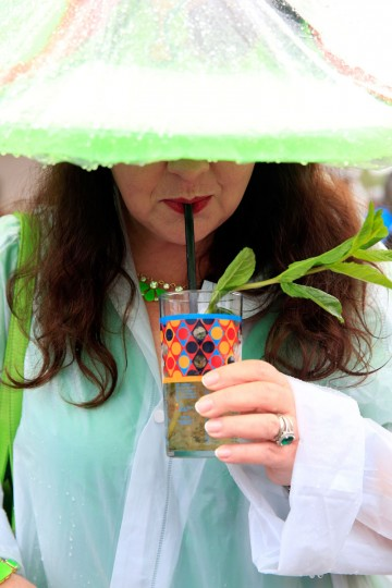 A race fan in a festive hat, enjoys a mint julep while it rains, prior to the 139th running of the Kentucky Derby at Churchill Downs in Louisville, Kentucky. (Jamie Squire/Getty Images)
