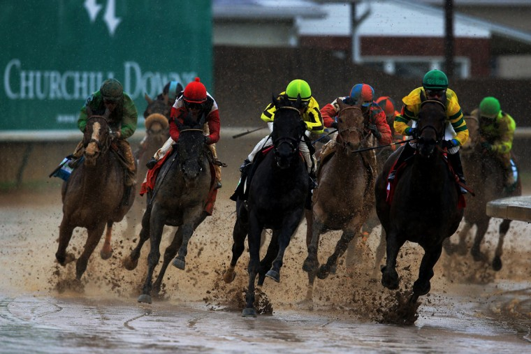 Horses race along the muddy backstretch during an undercard race prior to the 139th running of the Kentucky Derby at Churchill Downs in Louisville, Kentucky. (Doug Pensinger/Getty Images)