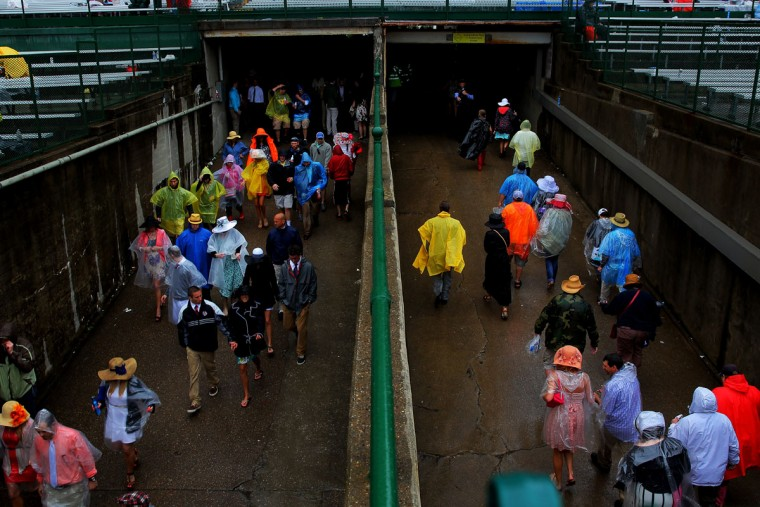 Race fans pass through a tunnel while taking cover from the rain prior to the 139th running of the Kentucky Derby at Churchill Downs on May 4, 2013 in Louisville, Kentucky. (Doug Pensinger/Getty Images)