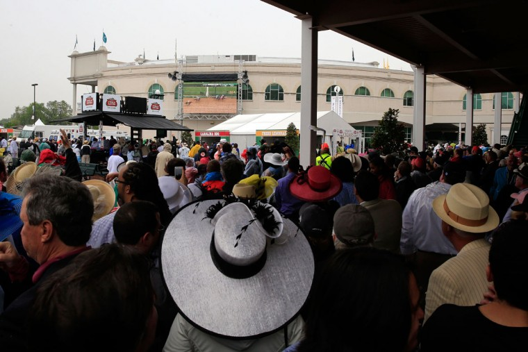 Race fans stand in the paddock, while it rains, prior to the 139th running of the Kentucky Derby at Churchill Downs on May 4, 2013 in Louisville, Kentucky. (Jamie Squire/Getty Images)