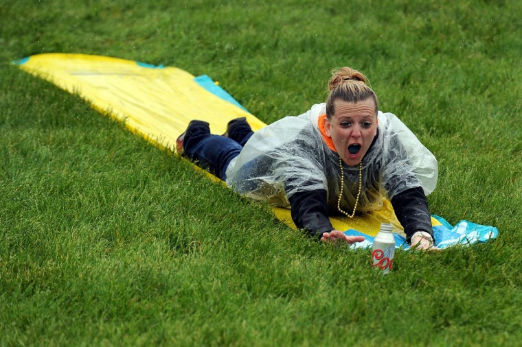 A race fan slides down a Slip N Slide in the infield, while it rains, prior to the 139th running of the Kentucky Derby at Churchill Downs in Louisville, Kentucky. (Jamey Price/Getty Images)
