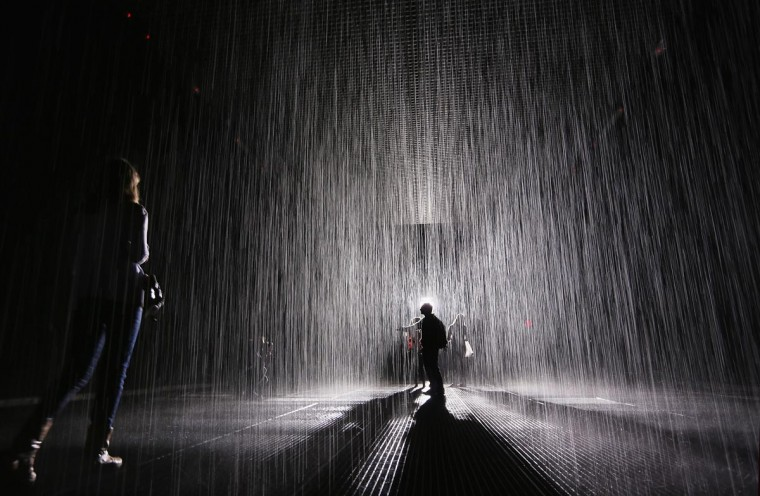 Visitors gather in the new 'Rain Room' installation at the Museum of Modern Art (MoMA) in Manhattan on May 15, 2013 in New York City. The 5,000 square-foot installation creates a field of falling water that stops in the area where people walk through, allowing them to remain dry. The piece, created by Random International, releases a 260-gallon per minute shower around visitors. (Mario Tama/Getty Images)