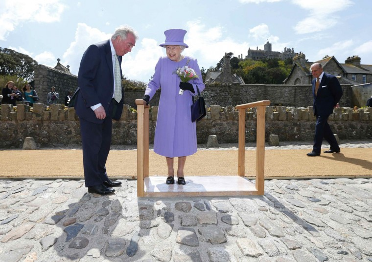 Queen Elizabeth II leaves an impression of her feet in a mould as Prince Philip, Duke of Edinburgh (R) looks on during their visit to St Michael's Mount, off the coast of Cornwall in south west England. Emily is the daughter of Gary Earrly, head of Cornish Heritage Builders, and was invited to receive the Queen and Duke of Edinburgh by the St Aubyn family who live on the island. (Andrew Winning - WPA Pool/Getty Images)