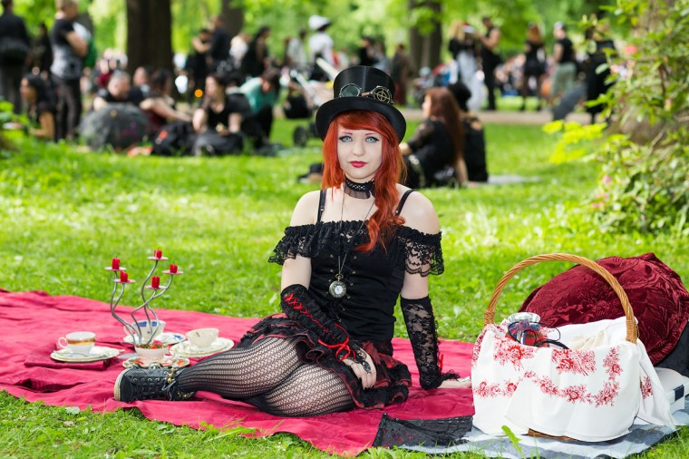 A girl sits on a red blanket on the lawn during the traditional park picnic on the first day of the annual Wave-Gotik Treffen, or Wave and Goth Festival, on May 17, 2013 in Leipzig, Germany. (Marco Prosch/Getty Images)