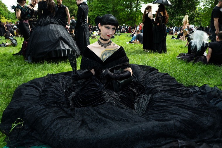 A woman in a black dress sits on the lawn during the traditional park picnic on the first day of the annual Wave-Gotik Treffen, or Wave and Goth Festival, on May 17, 2013 in Leipzig, Germany. (Marco Prosch/Getty Images)