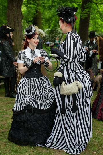 Two women in Victorian clothing and with a shawn-the-sheep-bag chat during the traditional park picnic on the first day of the annual Wave-Gotik Treffen, or Wave and Goth Festival, on May 17, 2013 in Leipzig, Germany. (Marco Prosch/Getty Images)