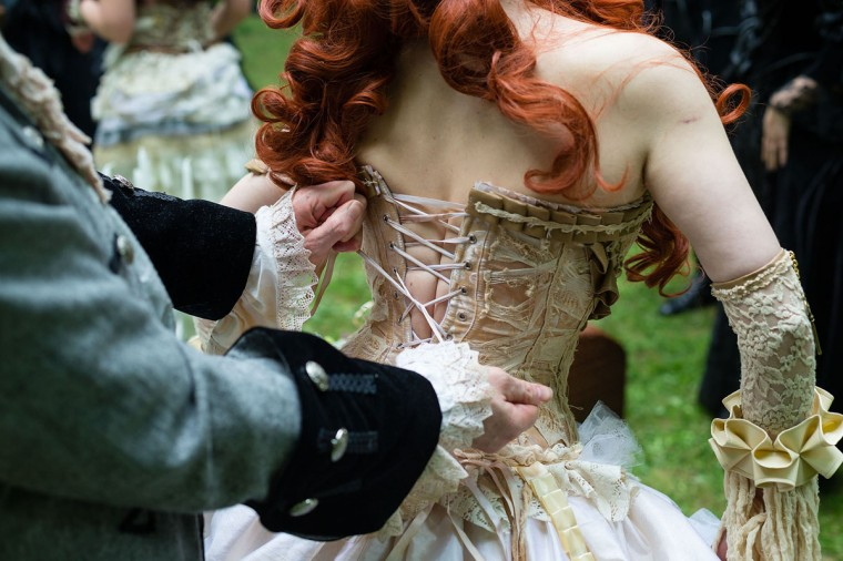 A man helps a woman straightening her corset during the traditional park picnic on the first day of the annual Wave-Gotik Treffen, or Wave and Goth Festival, on May 17, 2013 in Leipzig, Germany. (Marco Prosch/Getty Images)