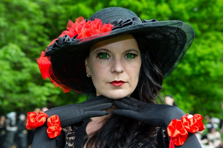 A woman with fake green eyes wearing hat and gloves poses for pictures during the traditional park picnic on the first day of the annual Wave-Gotik Treffen, or Wave and Goth Festival, on May 17, 2013 in Leipzig, Germany. (Marco Prosch/Getty Images)