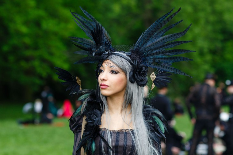 A woman in black clothing wearing a feather-hat poses for pictures during the traditional park picnic on the first day of the annual Wave-Gotik Treffen, or Wave and Goth Festival, on May 17, 2013 in Leipzig, Germany. (Marco Prosch/Getty Images)