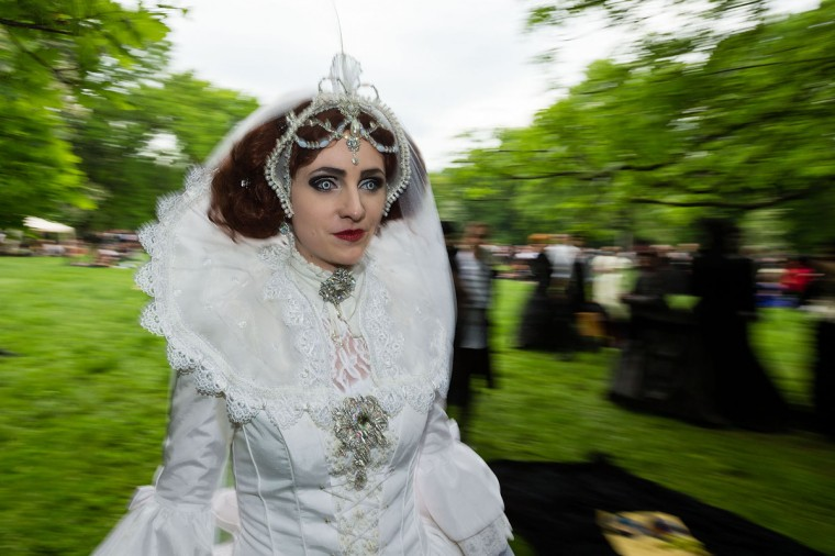 A woman in a white dress with fake wolf's eyes rushes by during the traditional park picnic on the first day of the annual Wave-Gotik Treffen, or Wave and Goth Festival, on May 17, 2013 in Leipzig, Germany. (Marco Prosch/Getty Images)