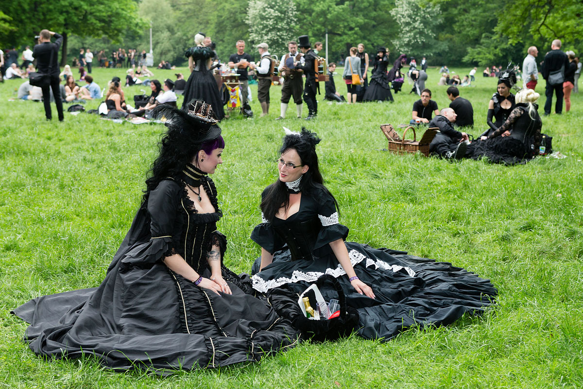 Two women in black Victorian clothing sit on the lawn and chat during