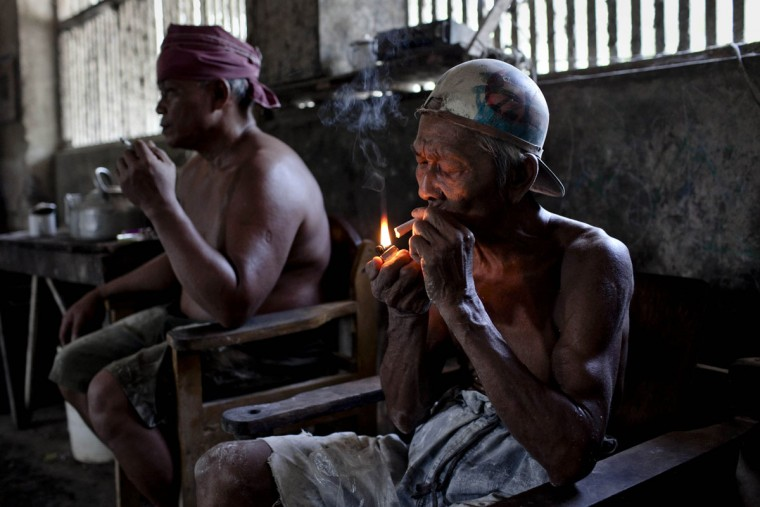 Workers smoke during a break at mie lethek factory in Srandakan village, Bantul on May 22, 2013 in Yogyakarta, Indonesia. Yasir Feri Ismatrada took on the family business of mie lethek production founded by his late grandfather. A one-ton stone cylinder is rotated by cows in order to grind the flour, a technique rarely seen today. Yasir puts great importance on the fair treatment of his 40 employees with management profits capped at 10%, prioritizing the interests of the staff. Mie lethek are sold for Rp 8,000 or US$80 cents per kilogram. (Ulet Ifansasti/Getty Images)
