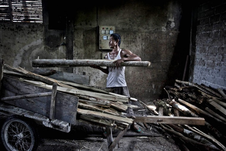 A worker carries firewood at mie lethek factory in Srandakan village, Bantul on May 22, 2013 in Yogyakarta, Indonesia. Yasir Feri Ismatrada took on the family business of mie lethek production founded by his late grandfather. A one-ton stone cylinder is rotated by cows in order to grind the flour, a technique rarely seen today. Yasir puts great importance on the fair treatment of his 40 employees with management profits capped at 10%, prioritizing the interests of the staff. Mie lethek are sold for Rp 8,000 or US$80 cents per kilogram. (Ulet Ifansasti/Getty Images)