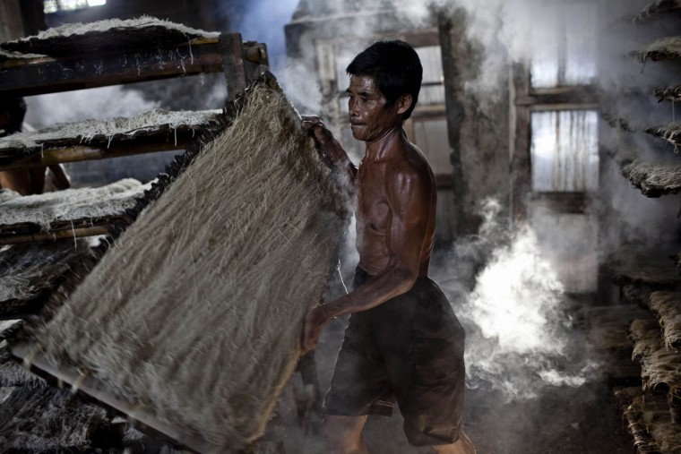A worker carries noodles or mie lethek after the steaming process at mie lethek factory in Srandakan village, Bantul on May 22, 2013 in Yogyakarta, Indonesia. Yasir Feri Ismatrada took on the family business of mie lethek production founded by his late grandfather. A one-ton stone cylinder is rotated by cows in order to grind the flour, a technique rarely seen today. Yasir puts great importance on the fair treatment of his 40 employees with management profits capped at 10%, prioritizing the interests of the staff. Mie lethek are sold for Rp 8,000 or US$80 cents per kilogram. (Ulet Ifansasti/Getty Images)