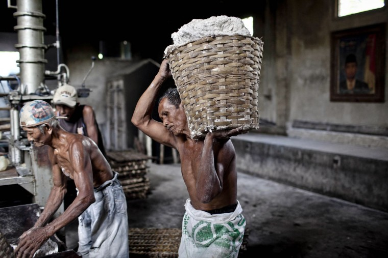 A worker carries a basket of dough after it was ground at mie lethek factory in Srandakan village, Bantul on May 22, 2013 in Yogyakarta, Indonesia. Yasir Feri Ismatrada took on the family business of mie lethek production founded by his late grandfather. A one-ton stone cylinder is rotated by cows in order to grind the flour, a technique rarely seen today. Yasir puts great importance on the fair treatment of his 40 employees with management profits capped at 10%, prioritizing the interests of the staff. Mie lethek are sold for Rp 8,000 or US$80 cents per kilogram. (Ulet Ifansasti/Getty Images)