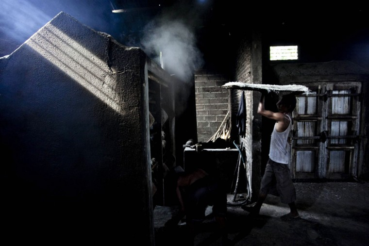 A worker carries noodles to be steamed at mie lethek factory in Srandakan village, Bantul on May 22, 2013 in Yogyakarta, Indonesia. Yasir Feri Ismatrada took on the family business of mie lethek production founded by his late grandfather. A one-ton stone cylinder is rotated by cows in order to grind the flour, a technique rarely seen today. Yasir puts great importance on the fair treatment of his 40 employees with management profits capped at 10%, prioritizing the interests of the staff. Mie lethek are sold for Rp 8,000 or US$80 cents per kilogram. (Ulet Ifansasti/Getty Images)