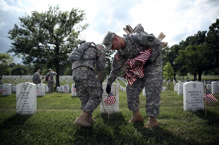 "Members of the Fife and Drum Corps of the 3rd U.S. Infantry Regiment, ""The Old Guard,"" participate in a ""Flags-In"" ceremony May 23, 2013 at Arlington National Cemetery in Arlington, Virginia. A small American flag was placed one foot in front of more than 220,000 graves in the cemetery to mark the Memorial Day. (Alex Wong/Getty Images)"