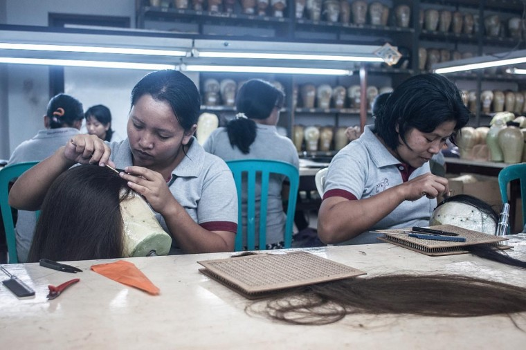 Members of staff knot hair to make theatrical and film wig on May 21, 2013 in Bangli, Bali, Indonesia at wig production company Sari Rambut. (Putu Sayoga/Getty Images)