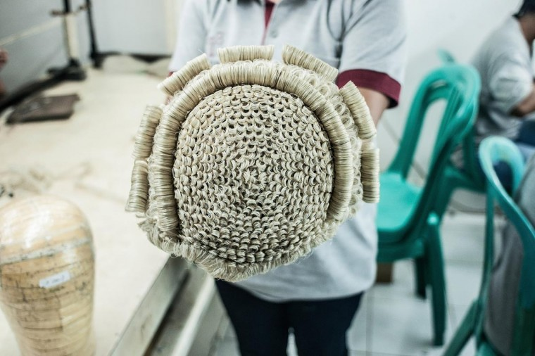 A member of staff shows already finished theatrical wig on May 21, 2013 in Bangli, Bali, Indonesia at Sari Rambut. (Putu Sayoga/Getty Images)