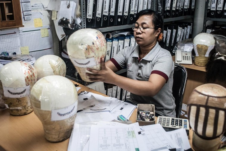 A member staff prepares a wig on May 21, 2013 in Bangli, Bali, Indonesia. (Putu Sayoga/Getty Images)