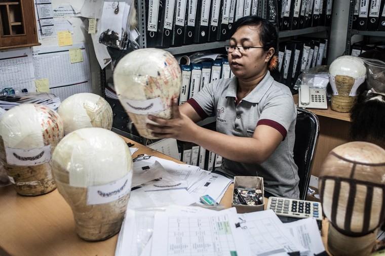 A member staff prepares a wig on May 21, 2013 in Bangli, Bali, Indonesia. (Putu Sayoga/Getty Images)