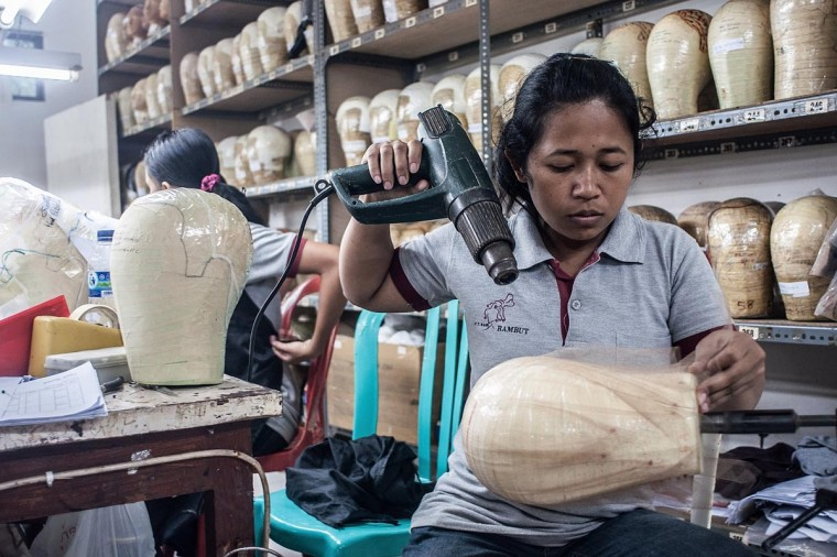 A member of staff makes a wig foundation on May 21, 2013 in Bangli, Bali, Indonesia. Sari Rambut wigs, which are produced in a workshop deep in the Ubud jungles of Bali, have been worn in some of the most high profile Hollywood & Broadway productions of recent years. (Putu Sayoga/Getty Images)