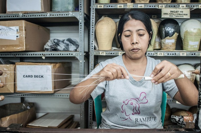 A staff rolls the hairs to make theatrical and film wigs on May 21, 2013 in Bangli, Bali, Indonesia at Sari Rambut. (Putu Sayoga/Getty Images)