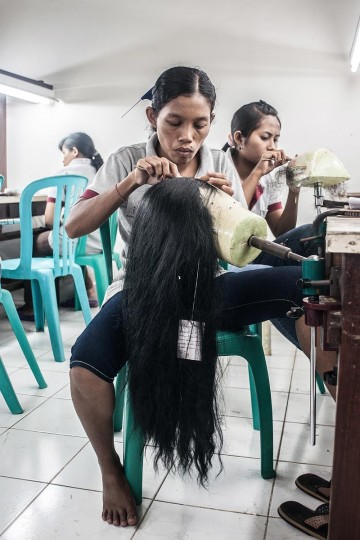 Employees knot hair on the wig foundation on May 21, 2013 in Bangli, Bali, Indonesia at Sari Rambut. (Putu Sayoga/Getty Images)