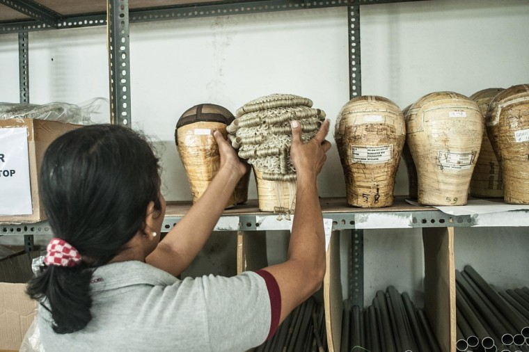 An employee places a completed wig on a shelf on May 21, 2013 in Bangli, Bali, Indonesia at Sari Rambut. (Putu Sayoga/Getty Images)