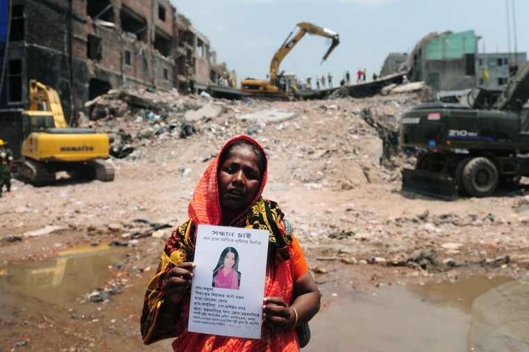 A Bangladeshi family member poses as she holds up the portrait of her missing relative, believed to be trapped in the rubble of an eight-storey building collapse in Savar, on the outskirts of Dhaka. The death toll from last week's collapse of a garment factory complex in Bangladesh has passed 500 as the country's prime minister said Western retailers had to share some of the blame for the tragedy. With bulldozers now clawing away at the mountain of rubble at the site of last Wednesday's disaster, the number of bodies being recovered from the country's deadliest industrial disaster has been increasing sharply. (Munir uz Zaman/AFP/Getty Images)