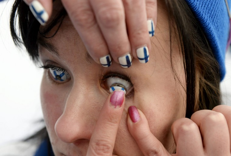 Finnish ice hockey fan Minna Westman puts on contact lenses with the finnish flag prior to the Ice Hockey game France vs Slovakia at the 2013 IIHF World Championships in Helsinki. (Lehtikuva/Martti Kainulainen/AFP/Getty Images)