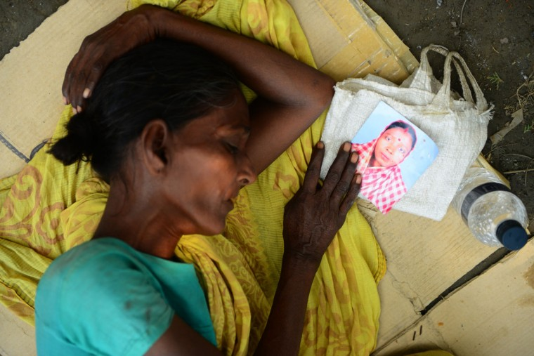 A Bangladeshi woman sleeps as she holds the portrait of her missing relative, believed to be trapped in the rubble of an eight-story building collapse in Savar, on the outskirts of Dhaka, on May 4, 2013. (Munir uz Zaman/AFP/Getty Images)