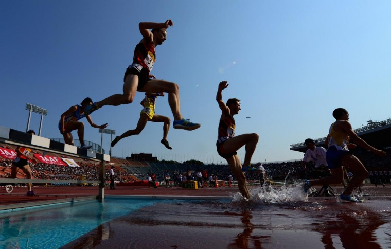 Runners jump over the water hazard in the men's 3000 metre steeplechase during the Seiko Golden Grand Prix in Tokyo on May 5, 2013. Jairus Kipcho Birech of Kenya won the race in 8 minutes 15.26 seconds. (Toru Yamanaka/AFP/Getty Images)
