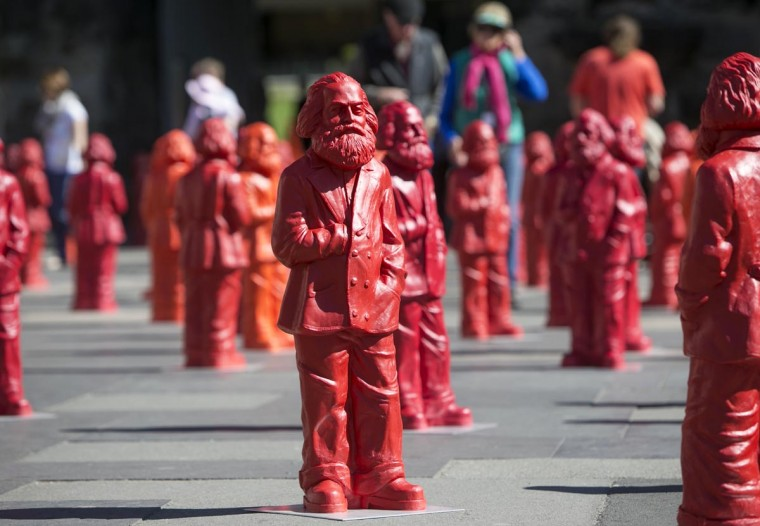 """Sculptures of the installation """"Karl Marx"""" made of 500 figures featuring the communist icon stand in front of the landmark Porta Nigra in Marx' native town Trier, southwestern Germany on May 5 , 2013. The installation by German artist Ottmar Hoerl is on display as part of the exhibition """"Icon Karl Marx"""" hosted at the City museum Simeonsstift on the occasion of the 130th anniversary of the death of Karl Marx. (Thomas Wieck/AFP/Getty Images)"""