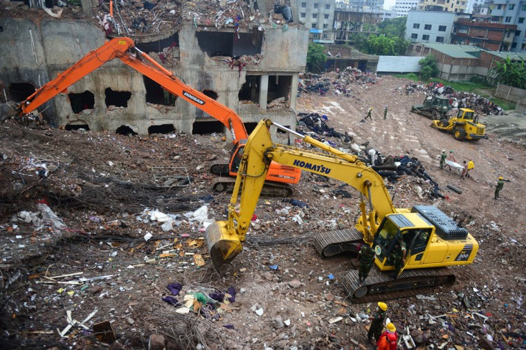 Bangladeshi rescue personnel carry stretchers with the remains of garment workers from the site of a collapsed building as heavy machinery clears the debris on the outskirts of Dhaka, on May 7, 2013. (Munir uz Zaman/AFP/Getty Images)