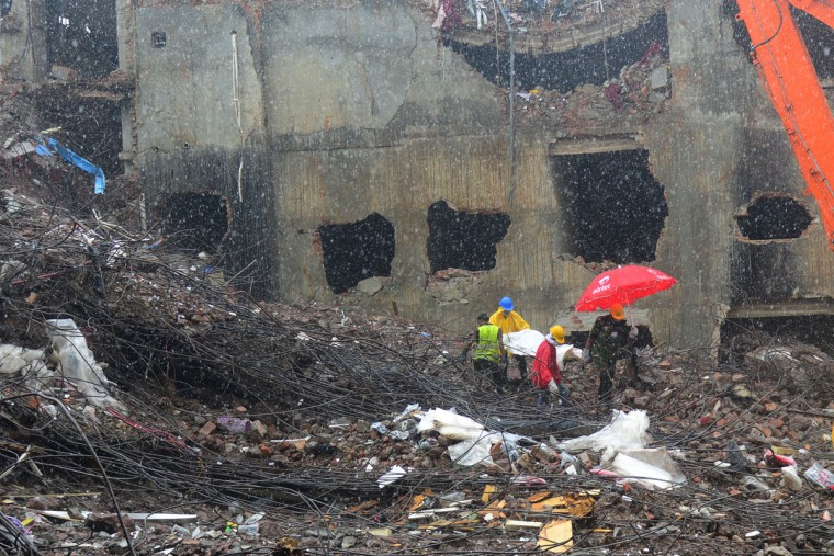 Bangladeshi rescue personnel carry stretchers with the remains of garment workers from the site of a collapsed building as heavy machinery clear the debris in Savar on the outskirts of Dhaka, on May 7, 2013. (Munir uz Zaman/AFP/Getty Images)