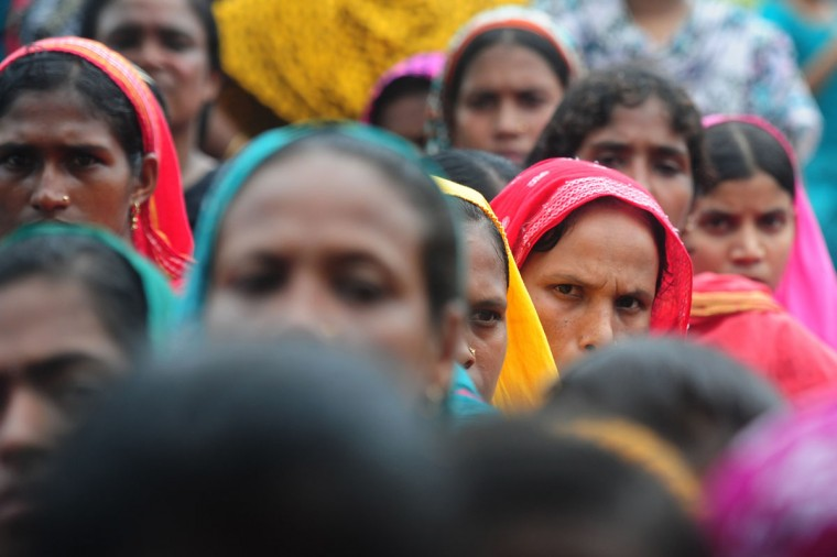 Bangladeshi garment workers, employed in the building which collapsed a fortnight ago, wait in line to claim their salaries in Savar on the outskirts of Dhaka, on May 8, 2013. The typical Bangladeshi garment worker takes home less than 40 dollars a month, a wage that Pope Francis has condemned as akin to slave labor. (Munir uz Zaman/AFP/Getty Images)