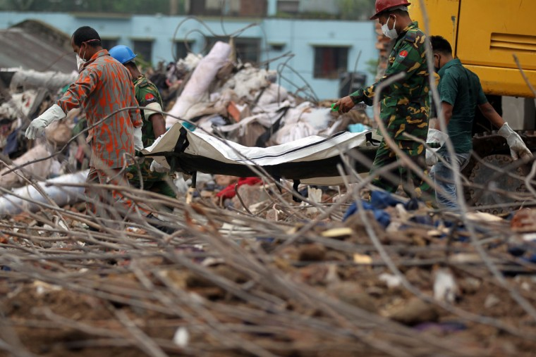 Bangladeshi rescue personnel carry stretchers with the remains of garment workers from the site of a collapsed building in Savar on the outskirts of Dhaka, on May 9, 2013. (STR/AFP/Getty Images)