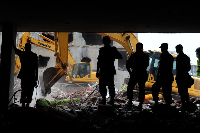 Bangladeshi Army personnel stand guard as they continue the second phase of the rescue operation using heavy equipment after an eight-story building collapsed on the outskirts of Dhaka. The death toll from last month's collapse of a garment factory complex in Bangladesh rose past 1,000 as piles of bodies were found in the ruins of a stairwell where victims had sought shelter. (Munir uz Zaman/AFP/Getty Images)