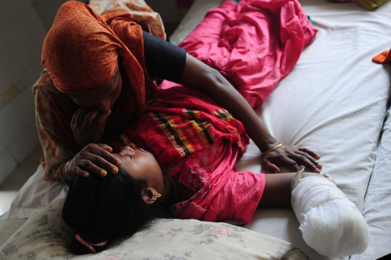 A young Bangladeshi garment worker who was rescued from a building that collapsed lies on a hospital bed with an amputated arm, in Savar, on the outskirts of Dhaka, on May 10, 2013. The death toll from last month's collapse of a garment factory complex in Bangladesh rose past 1,000 as piles of bodies were found in the ruins of a stairwell where victims had sought shelter. (Munir uz Zaman/AFP/Getty Images)