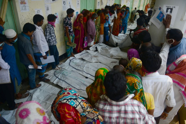 Relatives attempt to identify the bodies of loved ones killed in last week's building collapse in Savar, on the outskirts of Dhaka, on May 10, 2013. The death toll from last month's collapse of a garment factory complex in Bangladesh rose past 1,000 as piles of bodies were found in the ruins of a stairwell where victims had sought shelter. (Munir uz Zaman/AFP/Getty Images)