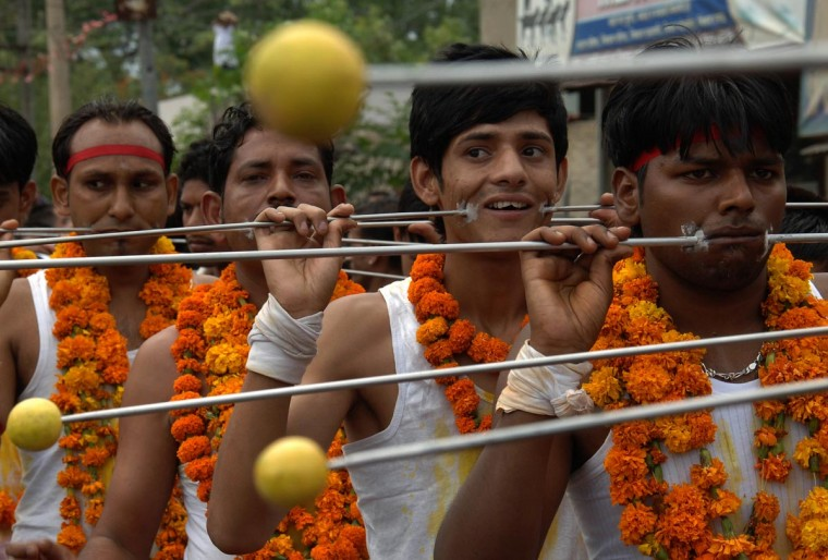 Indian Hindu devotees walk with trident rods piercing their cheeks while taking part in a procession held to honour the Hindu goddess Maha Mariamman in Amritsar on May 12, 2013. Devotees believe that the goddess protects whoever worships her. It is said she brings good health and prosperity to all her devotees. (Nanu Narinder/AFP/Getty Images)