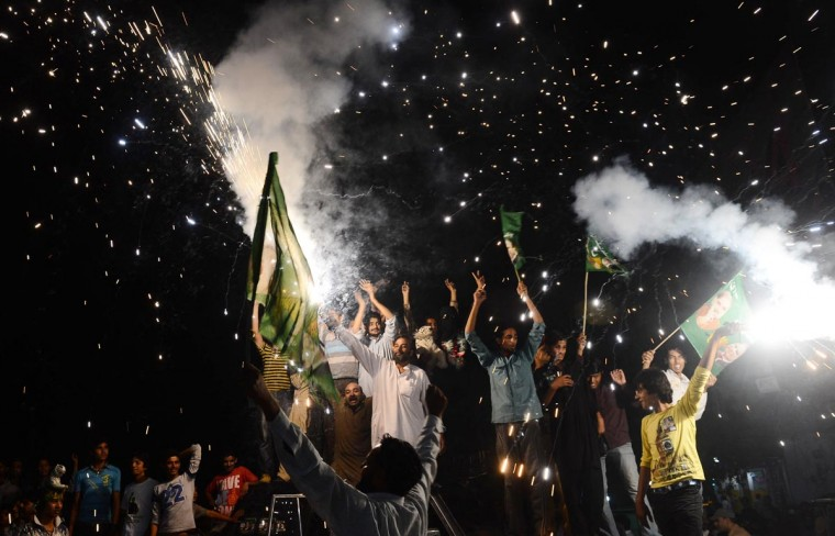 """Supporters of former Pakistani Prime Minister and head of the Pakistan Muslim League-N (PML-N), Nawaz Sharif, celebrate with fireworks the victory of their party a day after landmark general elections, in Lahore, on May 12, 2013. U.S. President Barack Obama welcomed the """"historic, peaceful and transparent transfer of civilian power"""", saying Washington was ready to work """"as equal partners"""" with the new government. (Arif Ali/AFP/Getty Images)"""