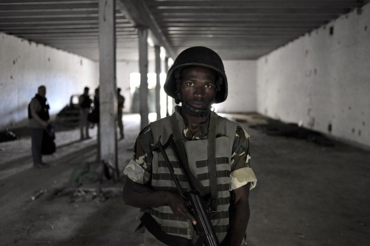 An Amisom soldier, as part of the Burundian contingent to the mission, stands guard at an underground bunker in Daynille, Somalia, on May 13, 2013. Humanitarian civilan EOD teams, with the support of Amisom, are currently in the process of emptying twenty-three bunkers in Daynille of explosives. The bunkers, remnants of the Siad Barre regime, still contain weapons which, if not destroyed, could pose a risk to civilians and provide bomb-making material for al Shabaab militants. (Tobin Jones/AU-UN IST via AFP/Getty Images)