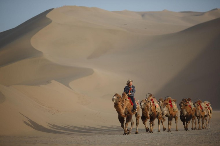 A guide leading camels near the Yueyaquan Crescent Lake in Dunhuang, in China's northwestern Gansu province on May 12, 2013. Formerly a silk route hub and center for trade between China and the West, Dunhuang relies heavily on tourism and features a number of historic sites dating back to the Han Dynasty. The city has an arid climate and is surrounded by sand dunes, a result of increasing desertification. (Ed Jones/AFP/Getty Images)