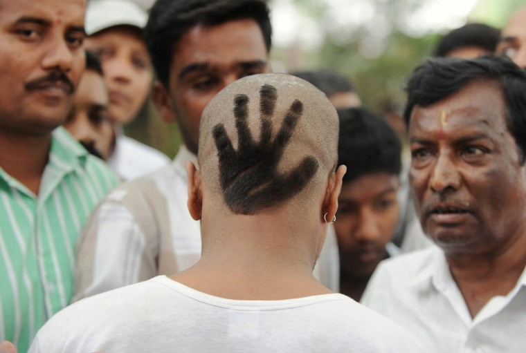 A Congress Party supporter displays his hair style featuring the party's symbol at the swearing-in ceremony of Karnataka Pradesh Congress Committee (KPCC) chief, Siddaramaiah as Karnataka chief minister in Bangalore on May 13, 2013. Congress leader Siddaramaiah takes over as 22nd Karnataka chief minister after leading his party to a huge win in last week's assembly elections, winning 121 seats in the 224-seat assembly. (Manjunath Kiran/AFP/Getty Images)
