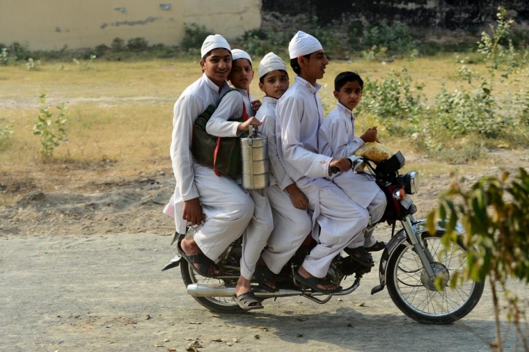 Four Pakistani brothers and a friend (L) crowd a motorcycle as they make their way home from school at a madrasa in Lahore on May 13, 2013. The boys were carrying a food container with a meal they were given to take to a worker at the mosque's local office nearby. (Roberto Schmidt/AFP/Getty Images)