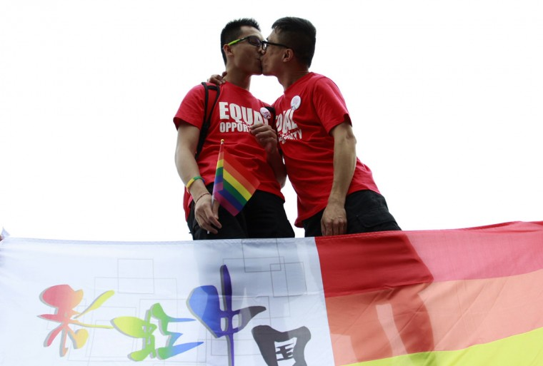 Two youngsters kiss each other behind a rainbow flag, a symbol for the homosexuals, during their anti-discrimination parade in Changsha, central China's Hunan province. About one hundred persons gathered to the anti-discrimination parade on the International Day Against Homophobia, appealing for understanding to homosexuals from the mass people. (STR/AFP/Getty Images ORG XMIT: