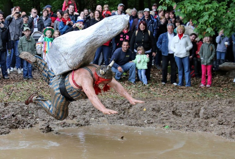 A participant jumps into a puddle of mud during the so-called 'Dirty Pig Festival' in Hergisdorf, Germany, on May 20, 2013. The people of Hergisdorf use the annual event to banish the winter season. (Jan Woitas/AFP/Getty Images)